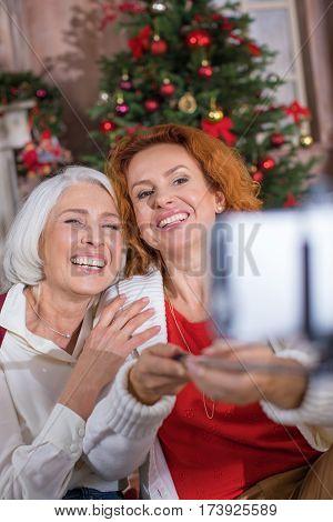 Two happy women taking selfie near the Christmas tree