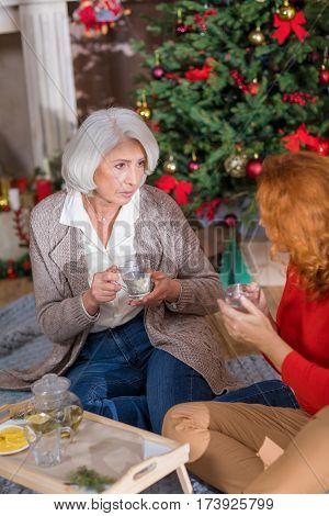Two women drinking tea sitting on the floor near Christmas tree