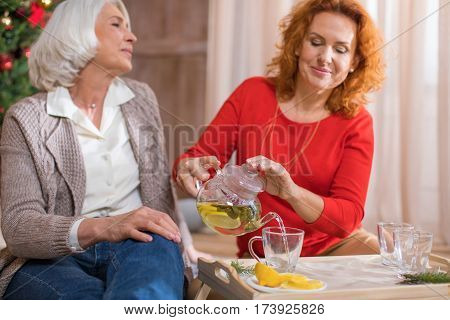 Two mature women pouring tea with lemon in glass cups