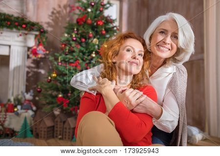 Two women embracing sitting on the floor near Christmas tree