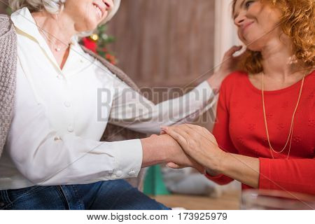 Woman holding hand of her senior mother