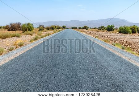 Clear road in Moroccan desert. Nobody is here. The mountains of Middle Atlas on horizon.