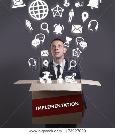 Business, Technology, Internet And Network Concept. Young Businessman Shows The Word: Implementation