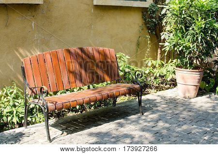 Empty Chair in the Flower Garden with Orang Wall Background.