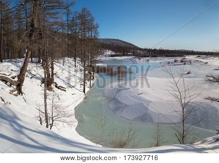 Winter landscape with a stream of blue and green water and white ice