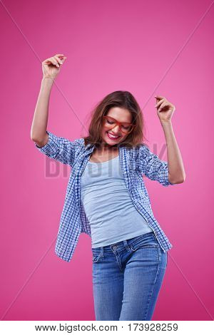 Mid shot of an exhilarate young hipster spends time with pleasure. Female posing over pink background