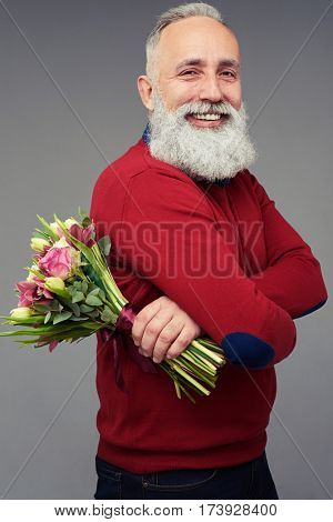 Side view shot of mature bearded man who is carrying a bouquet of flowers consisting of different tulips isolated over gray background