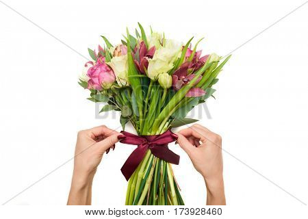 Close-up shot of hands tied the bouquet of spring flowers with a satin ribbon isolated over white background in the studio