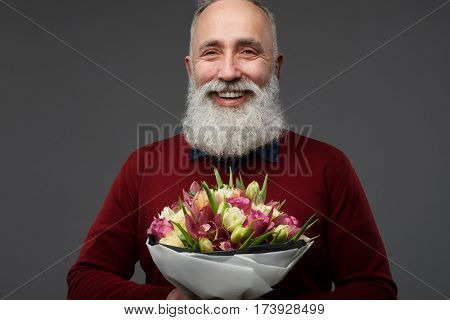 Close-up shot of mature man with a bouquet of different tulips isolated over gray background in the studio. International womens day