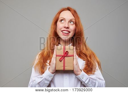 Close-up of dreamy teen thinking about something while holding a gift box in hands. Good-looking girl with auburn hair and freckles