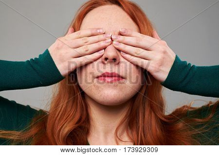 Close-up shot of young woman with auburn hair closes eyes with two hands isolated over gray background. Having fun in the studio