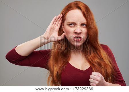 Close-up of angry woman eavesdropping gossip isolated over grey background. Anxious woman in vinous dress holding fist