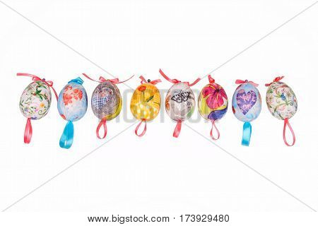 Colorful Easter decoupage eggs placed in line and isolated on white background