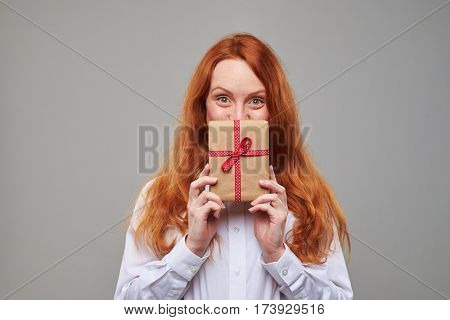 Close-up of pleased red hair girl peeps out the present box. Holding a wrapped gift box tied with a ribbon