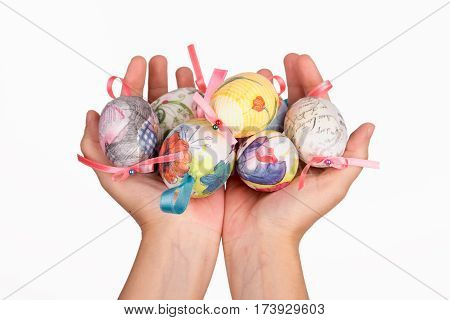 Colorful easter eggs in a clay hand isolated on white