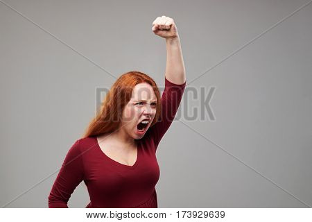 Close-up shot of a furious young woman with auburn hair holding fist above the head