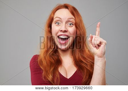 Close-up of exhilarated woman with raised index finger coming up with idea. Woman isolated over gray background