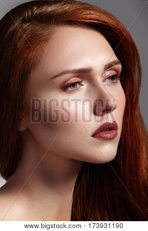 Beautiful ginger young woman with luxury hair style and fashion gloss makeup. Beauty portrait of sexy model with red hair. Long soft shiny hairstyle. Close-up studio shot of look redhead girl