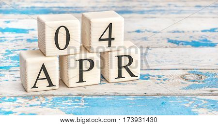 April 4th. Wooden cubes with date of 4 April on old blue wooden background.