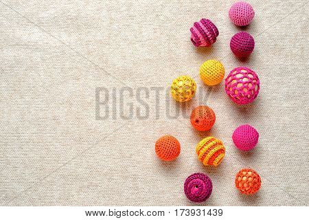 Multi-colored crocheted balls on a knitted background with copy space for your text