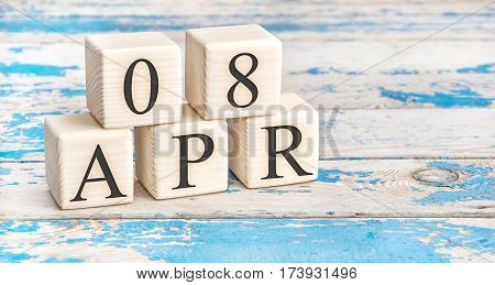 April 8th. Wooden cubes with date of 8 April on old blue wooden background.