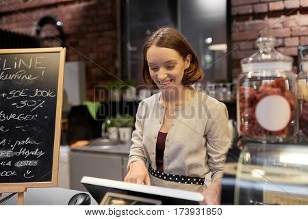 small business, people and service concept - happy woman or barmaid at counter with cashbox working in cafe or coffee shop