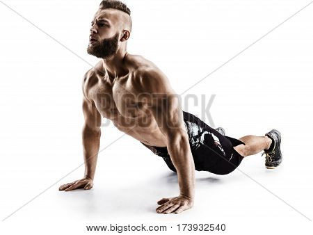 Handsome man doing push-ups exercises from the floor. Photo muscular man isolated on white background. The strength and motivation