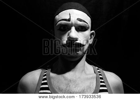 Funny portrait of theatrical mime on a black background