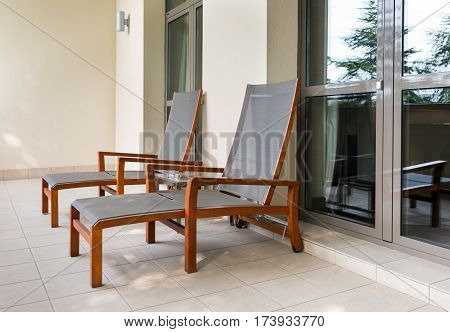 Two empty chaise longue and table on balcony of the hotel