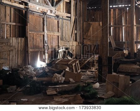 Rubbish garbage in an old wooden barn. Rays of light
