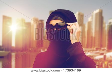 accessory, fashion and people concept - muslim woman in hijab and sunglasses over dubai city street background