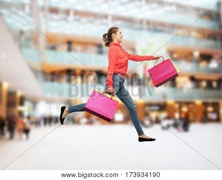 sale, motion and people concept - smiling young woman with shopping bags running in air over mall background