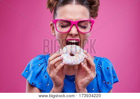 Close-up of beautiful woman biting greedily a sprinkled donut isolated over pink background. Girl with trimmed nails holding a donut