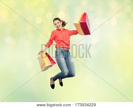 sale, motion and people concept - smiling young woman with shopping bags jumping in air over summer green lights background