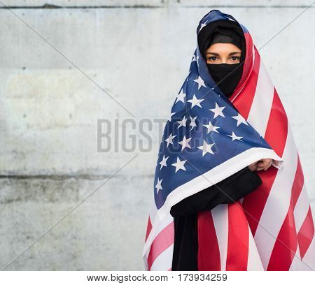 immigration and people concept - muslim woman in hijab with american flag over gray concrete wall background