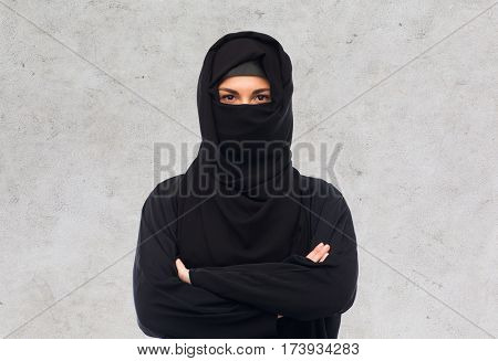 religious and people concept - muslim woman in hijab over gray concrete wall background