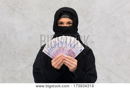 finances and people concept - muslim woman in hijab with money over gray concrete wall background