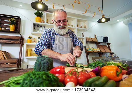 Low angle of smiling bearded man in a good mood preparing food for the dinner. Man wearing glasses preparing food. Colorful vegetables displaying on the table