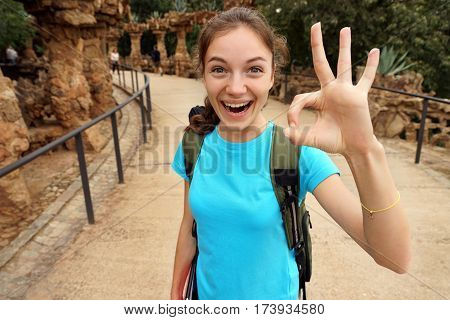 Happy tourist shows okay gesture. Young happy girl during her hike. Hiking. Travel in Spain.