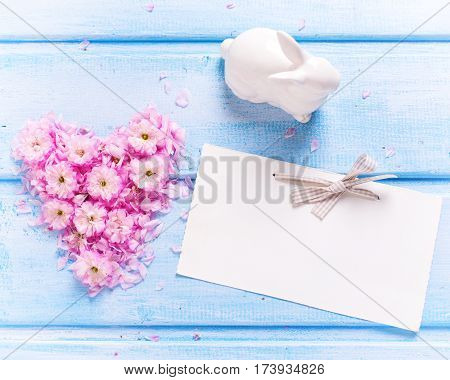 Heart from pink flowers and petals rabbit and empty tag on blue wooden planks. Selective focus. Place for text. Toned image.