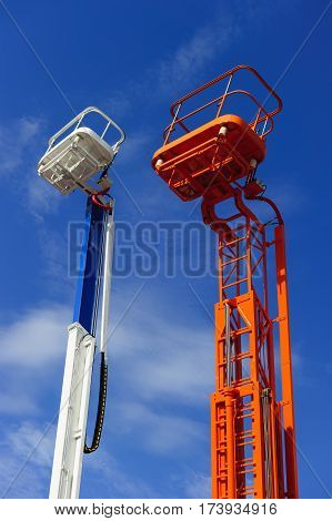 Lift platform with bucket and cherry picker aerial work platforms, construction hydraulic telescopic cranes of orange and white colors, heavy industry, blue sky on background