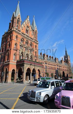 LONDON, UK - FEBRUARY 28, 2017: Exterior view of St Pancras Railway Station with taxis in the foreground. This building  now houses the luxury St Pancras Renaissance Hotel