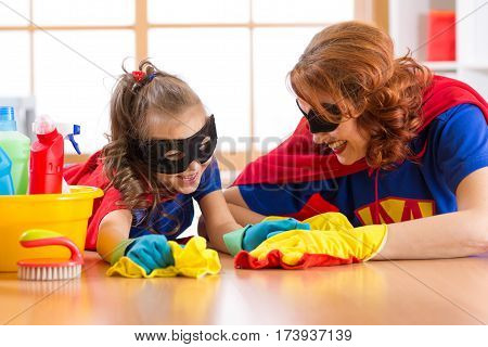 Cute woman and her child daughter dressed like superheroes cleaning the floor and smiling