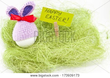 Easter Eggs On Green Sisal. Knitted Easter Bunny. Egg In Easter Bunny Cap.
