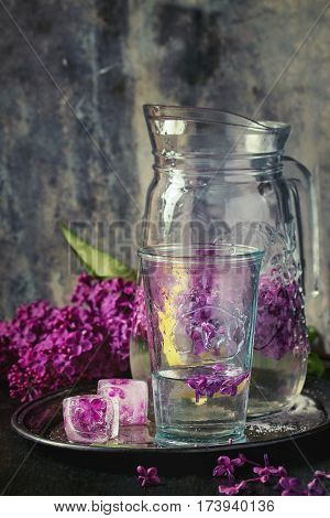 Glass and pitcher of lilac lemonade water  with lemon, ice cubes with lilac flowers and lilac branch on vintage iron tray over black wooden table. Dark rustic style.
