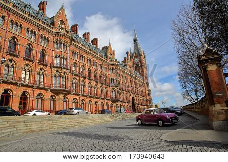 LONDON, UK - FEBRUARY 28, 2017: Exterior view of St Pancras Railway Station with a cobbled pavement and a purple classic car in the foreground. This building  now houses the luxury St Pancras Renaissance Hotel