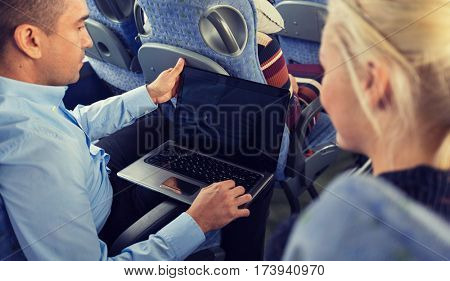transport, tourism, road trip, technology and people concept - close up of passengers couple with laptop in travel bus