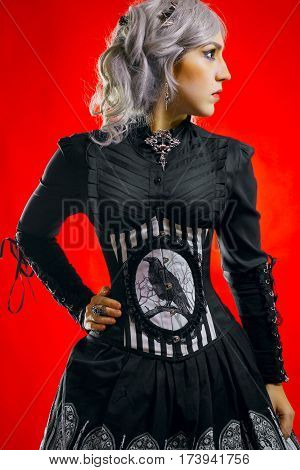 Pretty gothic girl with black eyes standing over red background