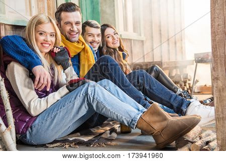 side view of happy friends sitting together and looking to camera