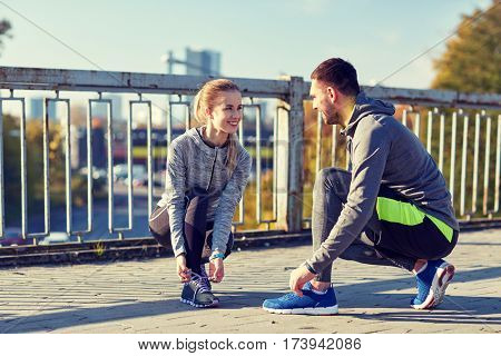 fitness, sport, people and lifestyle concept - smiling couple tying shoelaces outdoors